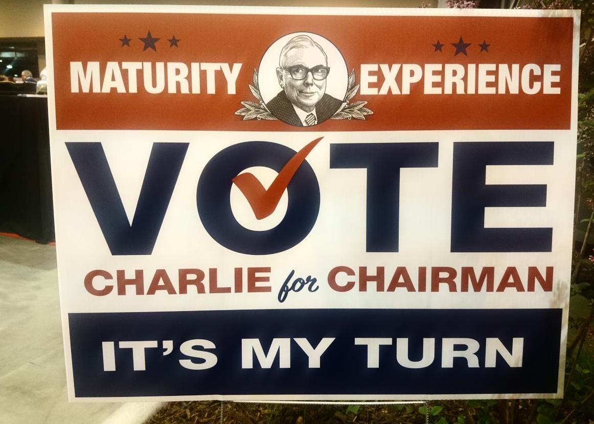 Charlie Munger je dlouholetým zástupcem Warrena Buffetta, žertovná cedule tak vybízí investory, aby do čela společnosti tentokrát zvolili jeho: jako staršího a tedy i zkušenějšího