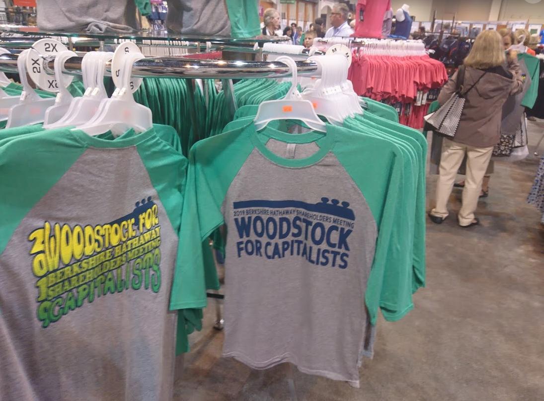 """Valné hromadě Berkshire Hathaway se občas přezdívá """"Woodstock pro kapitalisty"""", a tak se tento nápis dostal také na některá trička"""