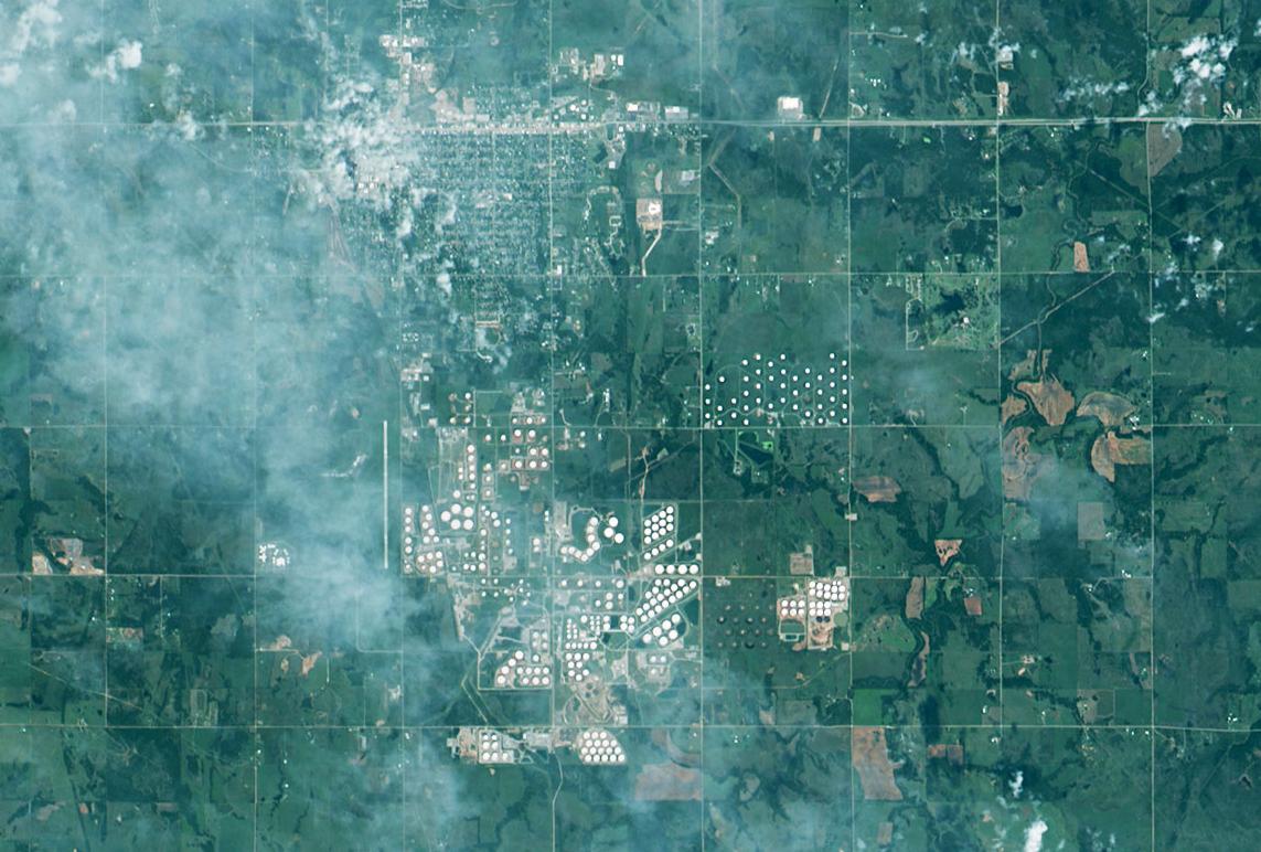 Letecký snímek městečka Cushing (nahoře) a ropných zásobníků (bílá kolečka dole), autor snímku: xelspace Corporation, CC BY-SA 4.0